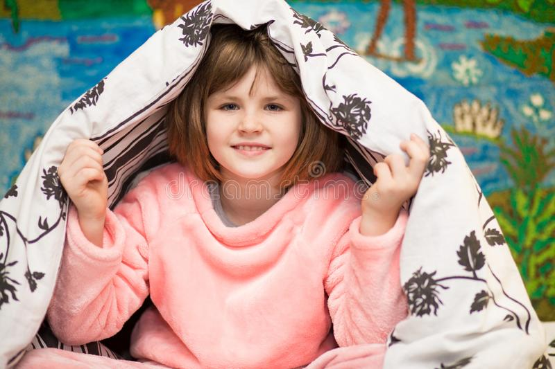 Little cheerful girl hides under blanket. Sweet girl having fun on bed. Concept of kids sleep. Care or childhood stock photography