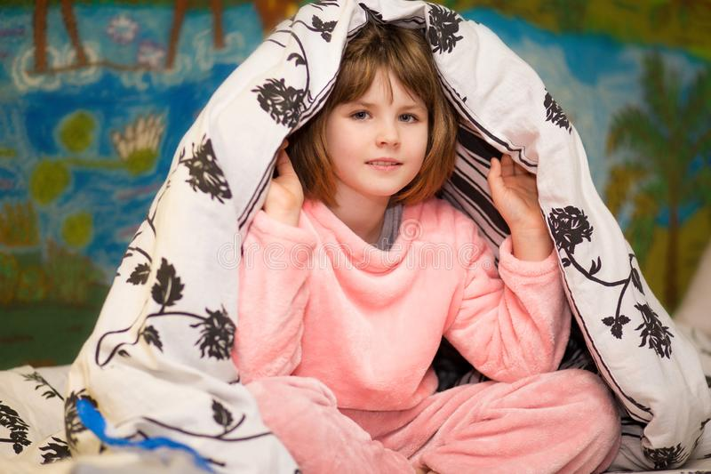 Little cheerful girl hides under blanket. Sweet girl having fun on bed. Concept of kids sleep. Care or childhood royalty free stock photo