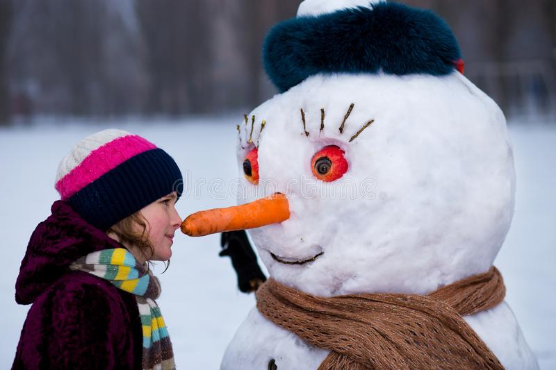 A little cheerful girl look at funny snowman face royalty free stock image