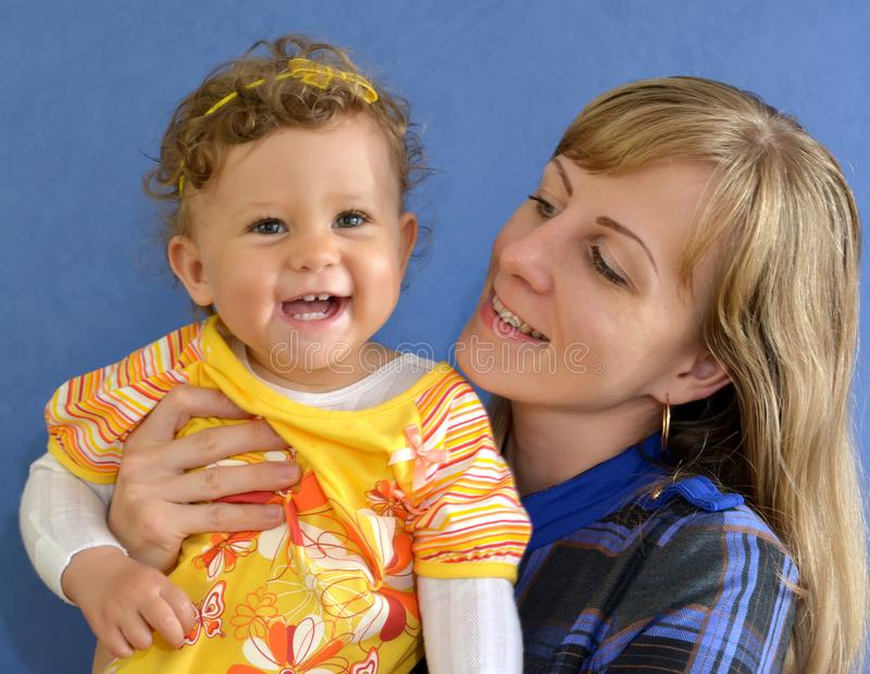 The little cheerful girl with mother on a blue background. Portrait stock photography