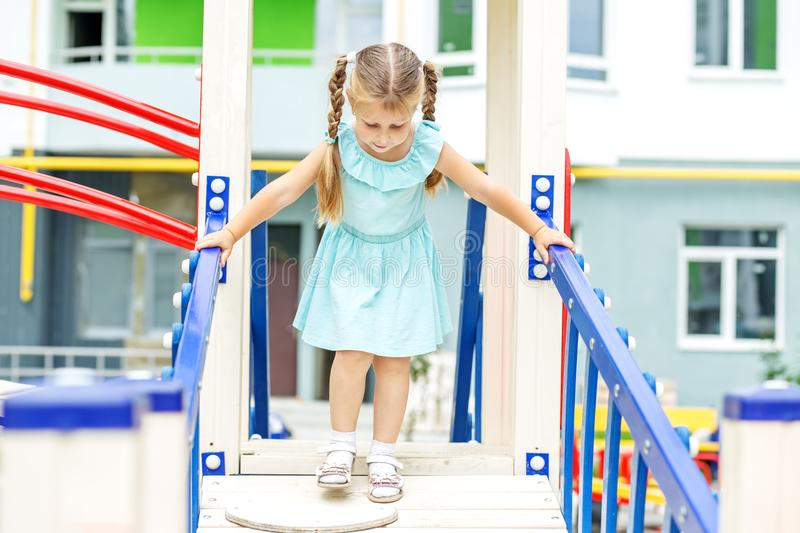 Little cheerful girl plays on the playground. The concept of childhood, lifestyle, upbringing, kindergarten. Little cheerful girl plays on the playground. The royalty free stock images