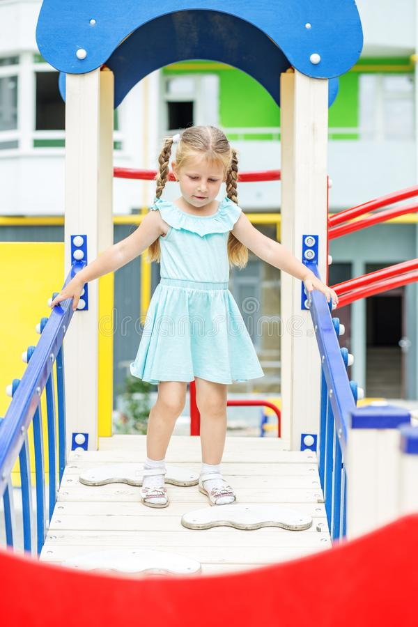 Little cheerful girl plays on the playground. The concept of childhood, lifestyle, upbringing, kindergarten. Little cheerful girl plays on the playground. The royalty free stock photography