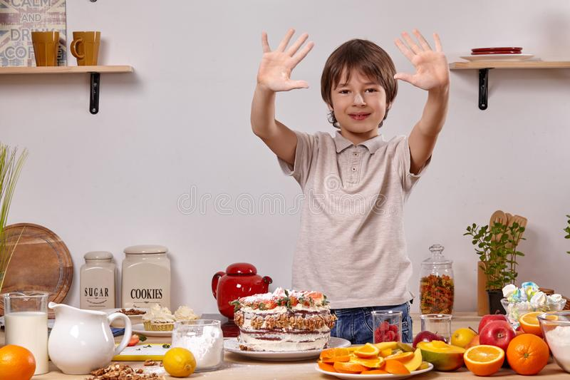 Little boy is making a homemade cake with an easy recipe at kitchen against a white wall with shelves on it. Little cheerful kid with smeared in powdered sugar stock photos