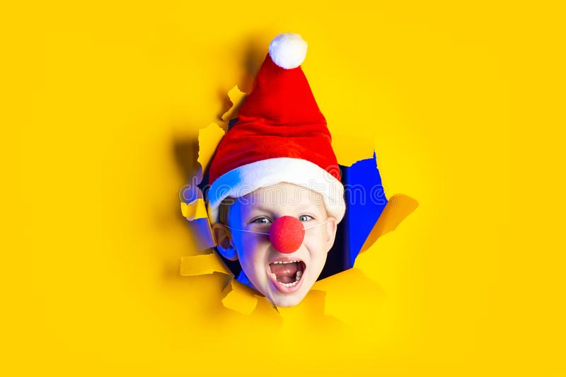 Little cheerful Santa in hat smiles, getting out of the ragged yellow background lit by neon light. Little cheerful Santa in a hat smiles, getting out of the stock photo
