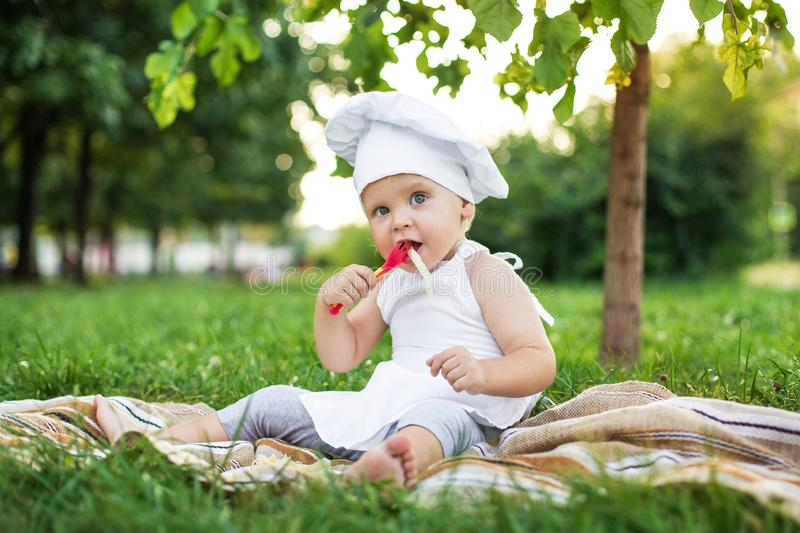 Little chef cooks and eats pasta on a picnic outdoors. Cute baby in a cook suit with pan and fork on the green nature bokeh royalty free stock image