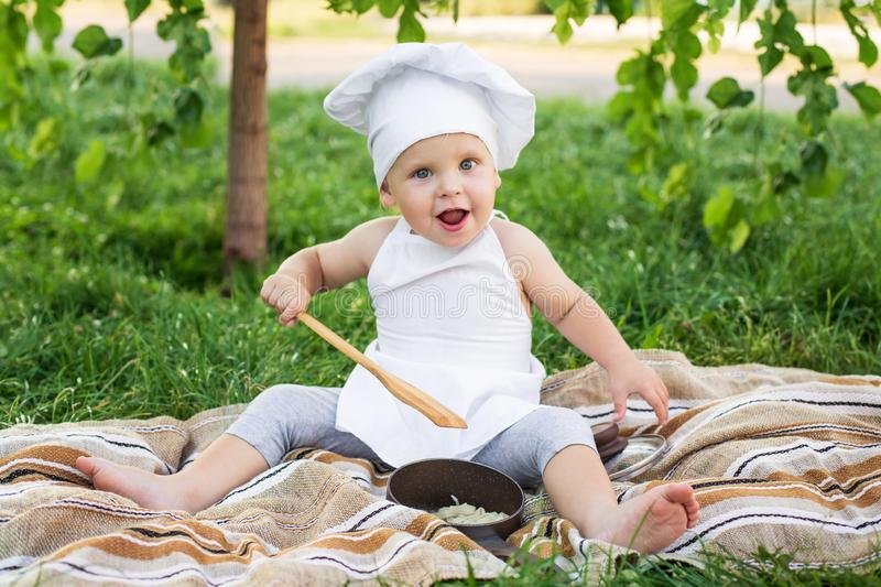Little chef cooks and eats pasta on a picnic outdoors. Funny baby in a cook suit with pan and cooking spatula on the green nature stock images