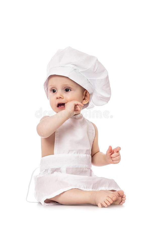 Little Chef. funny baby emotions. Adorable baby boy dressed in s chef`s hat. Cooking child lifestyle concept. Toddler playing. Isolated on white. Food banner royalty free stock photo
