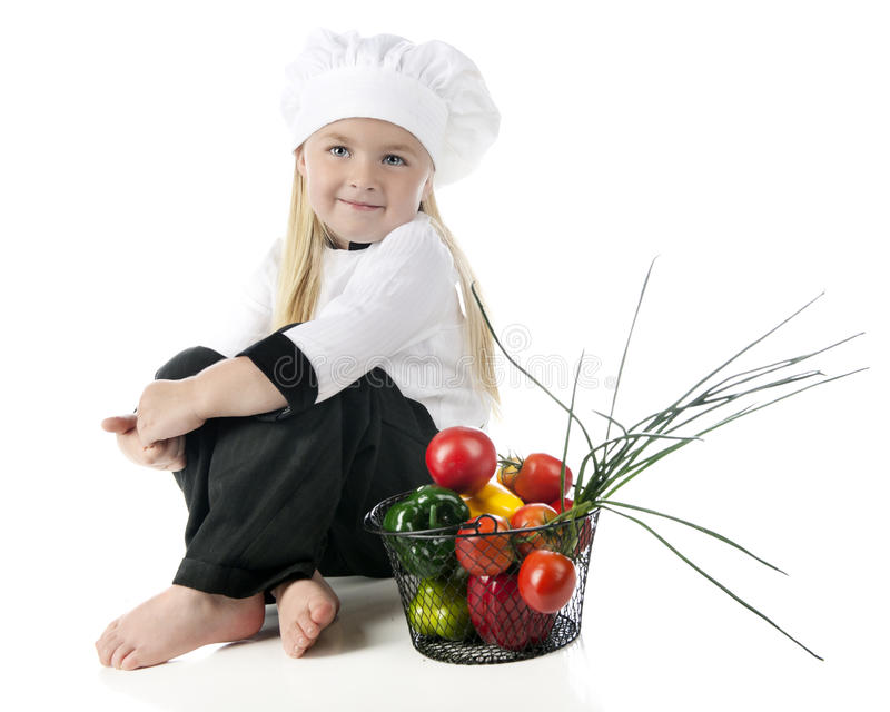 Little Chef by Her Veggies. A beautiful little chef happily sitting barefoot in her chef's outfit by a basket fulled with fresh veggies. On a white background royalty free stock images