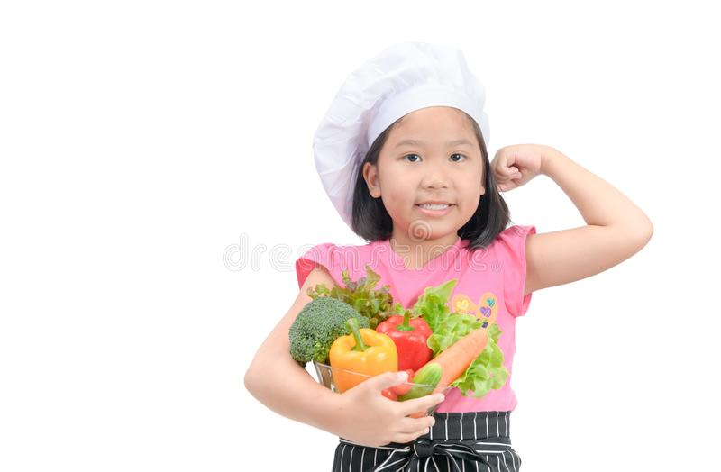 Little chef holding vegetables and show muscle royalty free stock image