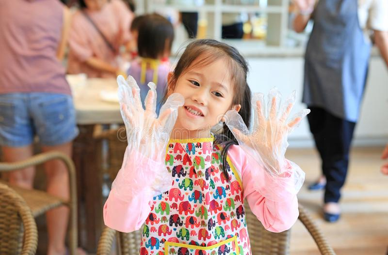 Little Chef wearing transparent plastic gloves in hands while cooking in the kitchen.  royalty free stock photo