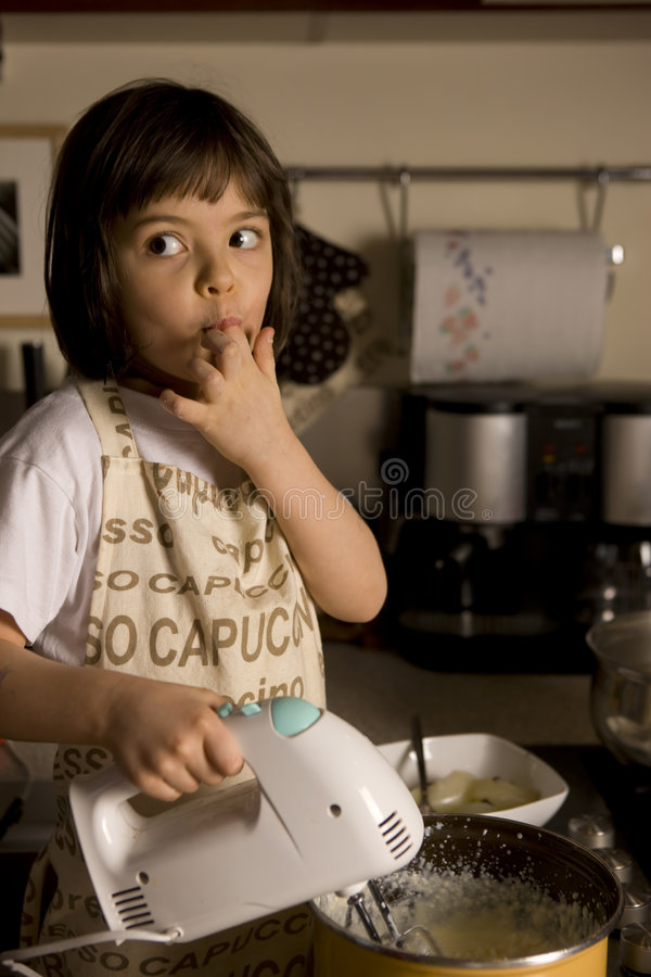 Little Chefs. Young girl having fun in the kitchen making cookies stock image