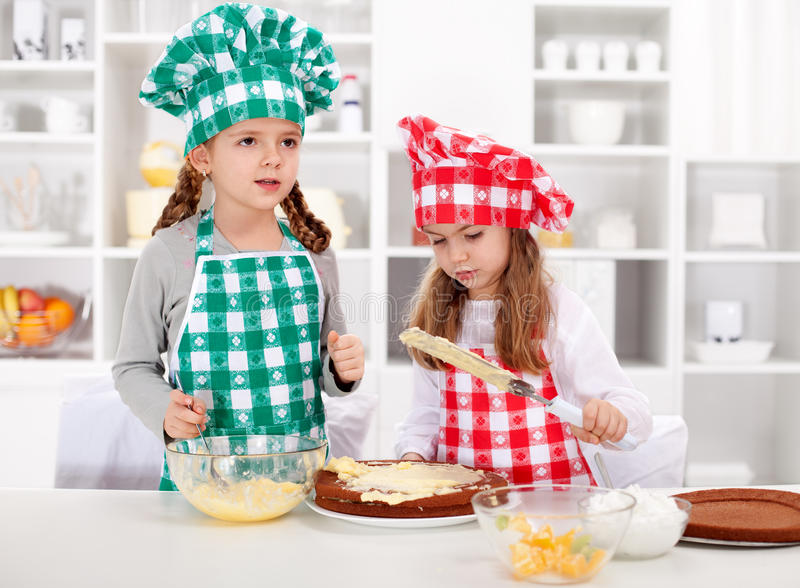 Little chefs making a cake. Covering the layers with cream royalty free stock image