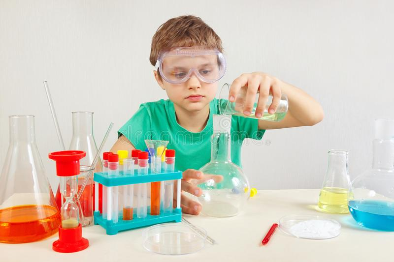 Little chemist in safety goggles doing chemical experiments in laboratory. Little chemist in safety goggles doing chemical experiments in the laboratory royalty free stock photography