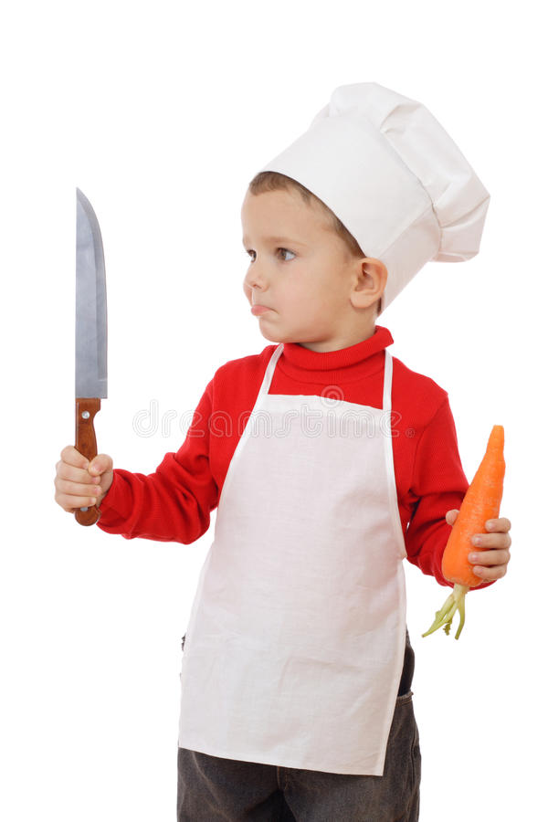 Little chief-cooker with kitchen knife and carrot royalty free stock photography