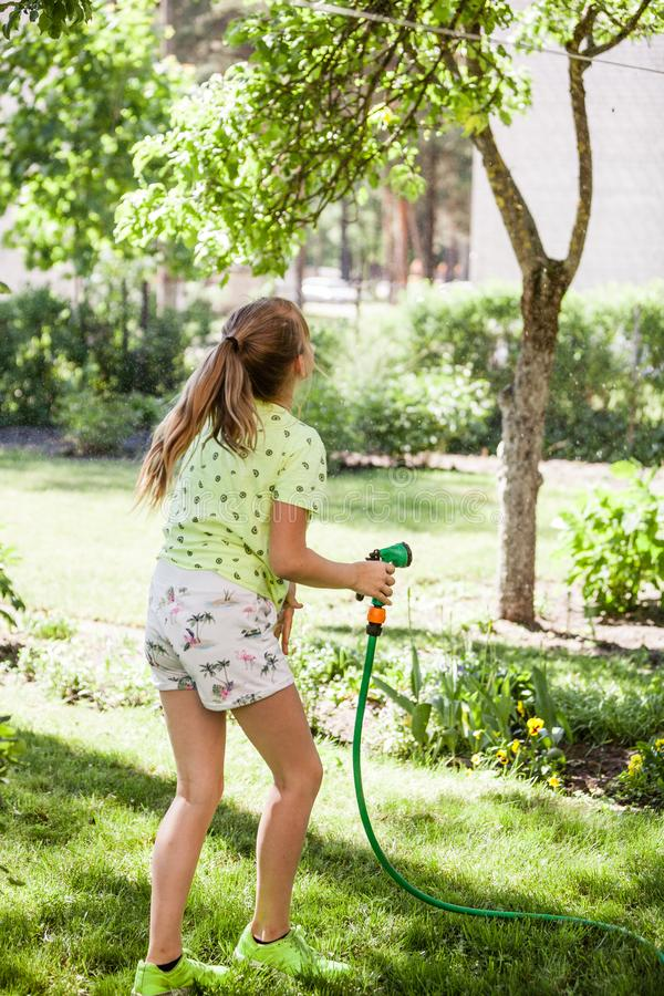 Little child, adorable blonde teen girl, watering the plants, beautiful flowers, from hose spray in the garden stock photography