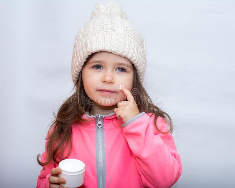 Little child applying cold cream to her face. Winter care. Little child applying cold wind and wetter cream or lotion to her face stock photography