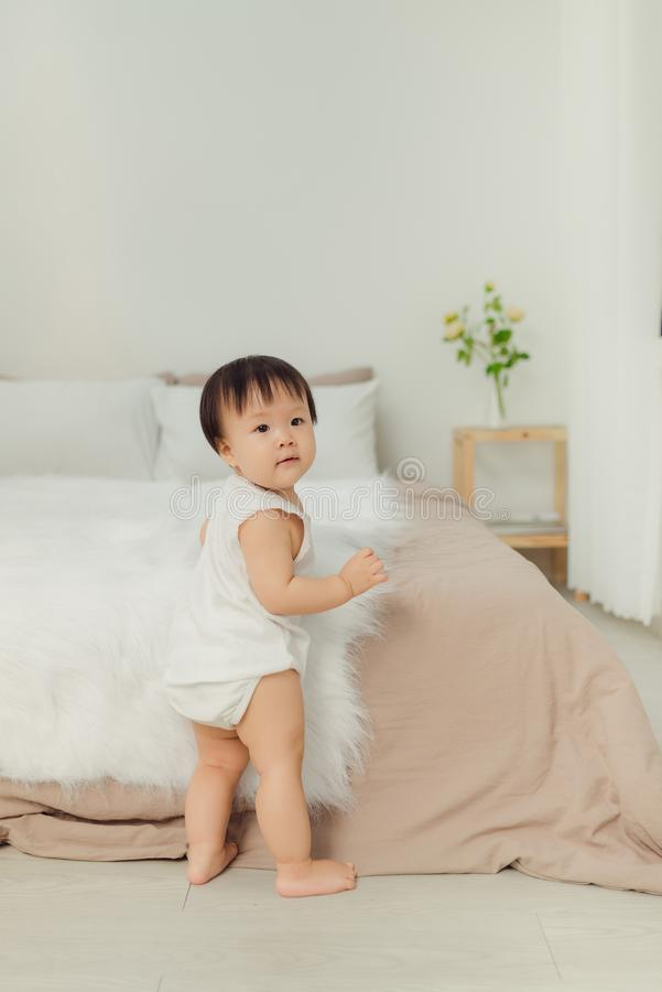 Little child baby boy close up, standing near bed in bedroom royalty free stock photo