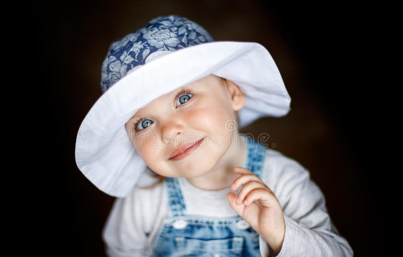 Little child baby smiling. Baby in a hat. Baby smiling close-up. Happy two year old girl. stock photo