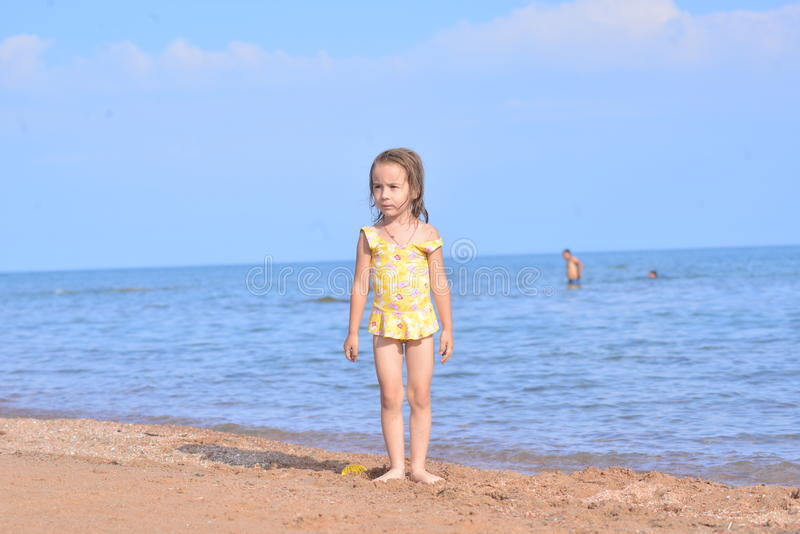 Little child on the beach in sunlight. Beach activity in summer vacation, baby on the coast royalty free stock image