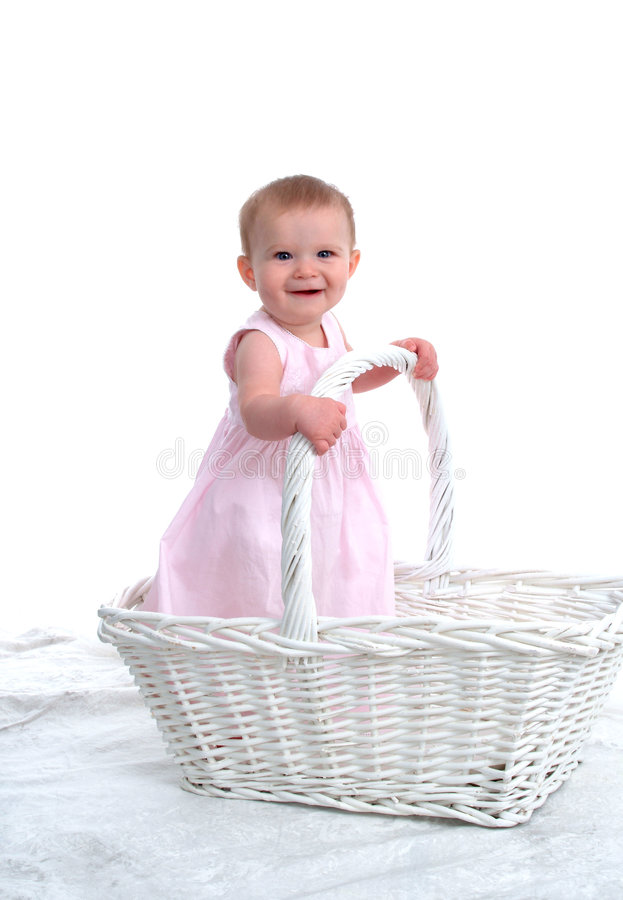 Little Child in a Big Basket. Smiling baby girl standing in a big wicker basket royalty free stock image