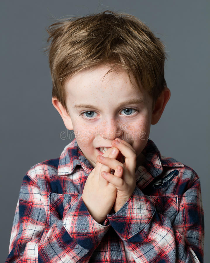 Little child biting fingers for boredom, stress or bad habit. Thoughtful little red hair child with freckles staring, biting his fingers for boredom, stress or royalty free stock photo