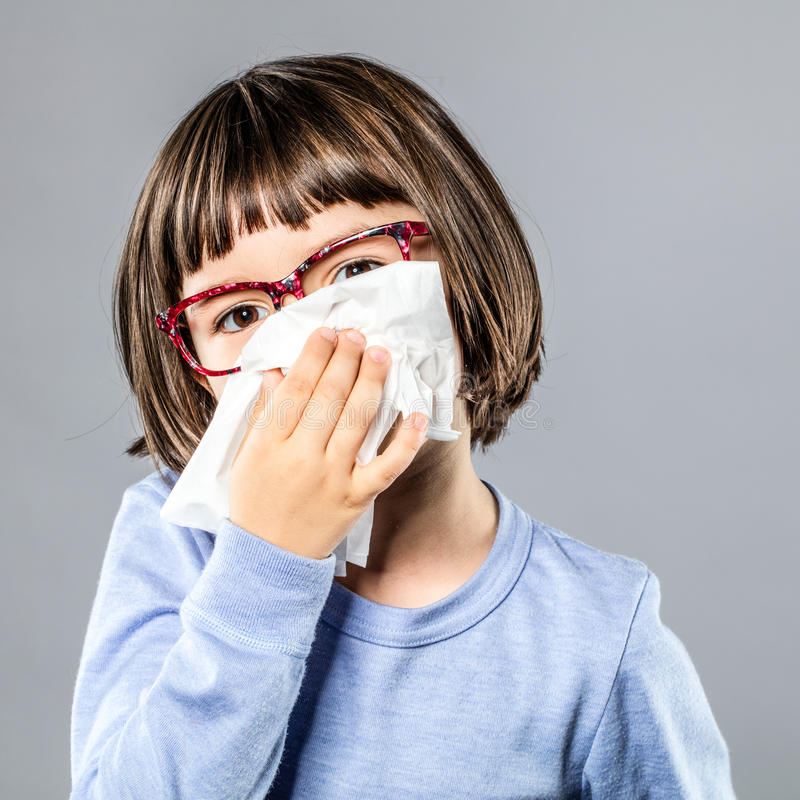Little child blowing nose in tissue for cold or allergies royalty free stock photo