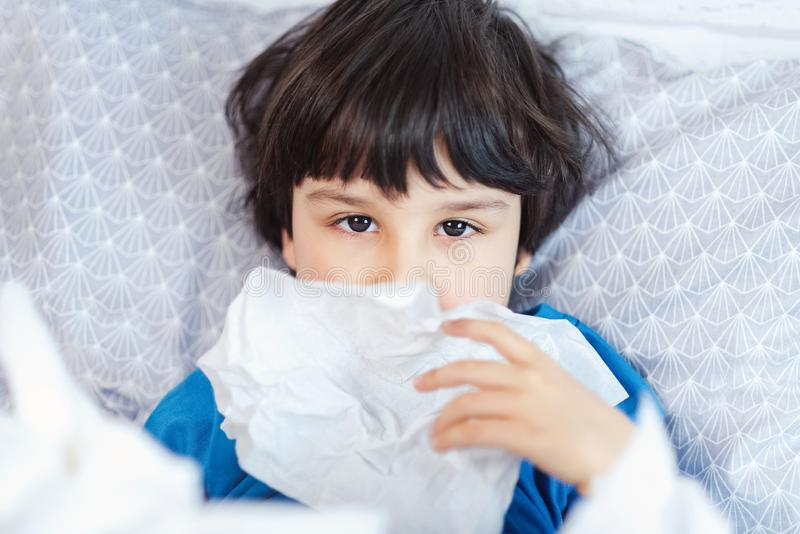 Little child boy blow his nose. Sick child with napkin in bed. Allergic kid, flu season. Kid with cold rhinitis, get cold royalty free stock photos