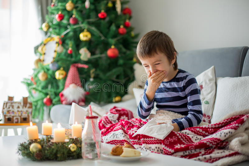 Little child, boy, blowing his nose and sneezing, lying sick in royalty free stock photography