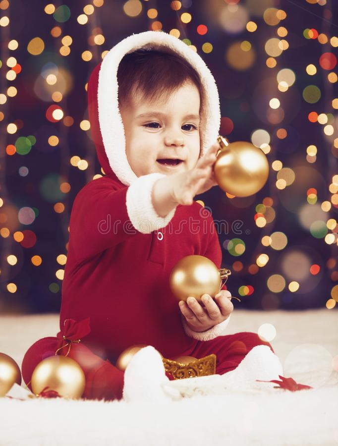 Little child boy dressed as santa playing with christmas decoration, dark background with illumination and boke lights, winter hol. Iday concept royalty free stock photography