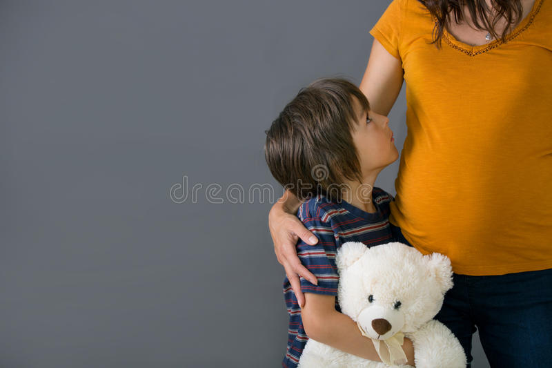 Little child, boy, hugging his pregnant mother at home, isolated. Image, copy space. Family concept royalty free stock image