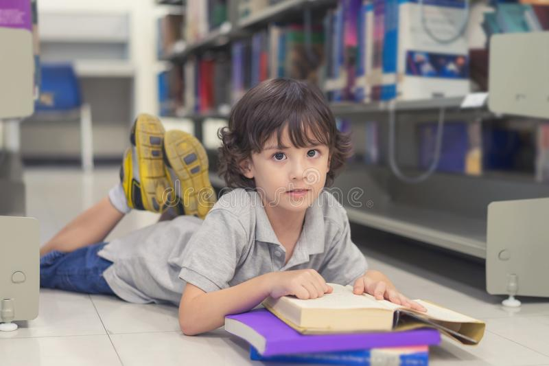 Little child boy laying on floor and reading a book in library. stock images