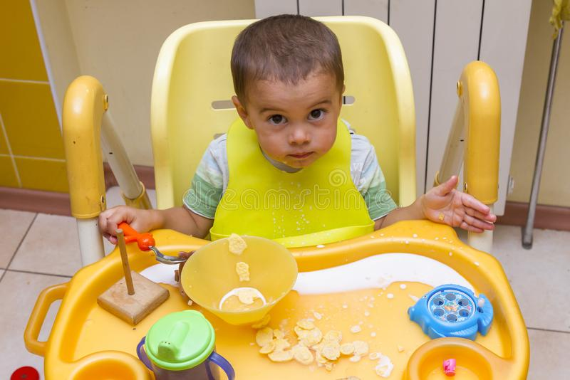 Little child boy learns to eat at the children& x27;s table in the kitchen. Baby eats funny. Little baby eats with a spoon soup royalty free stock photography