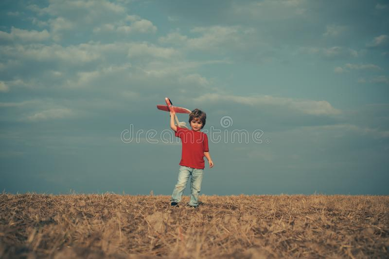Little child boy is playing and dreaming of flying over the clouds. Cute child playing with toy airplane in the meadow. In vintage color tone. Childhood concept stock photo