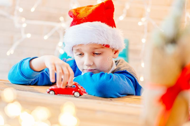 Little child boy playing with red toy car. Little child boy playing with small red toy car - a Christmas present royalty free stock photography