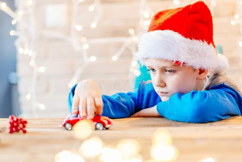 Little child boy playing with red toy car. Little child boy playing with small red toy car - a Christmas present stock photo