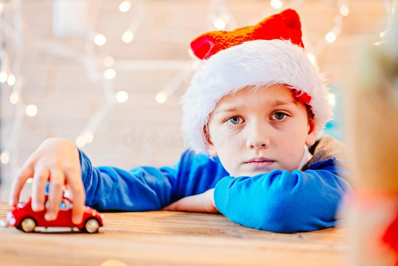 Little child boy playing with red toy car. Little child boy playing with small red toy car - a Christmas present stock image