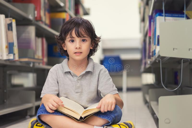 Little child boy reading a book in library. stock photos