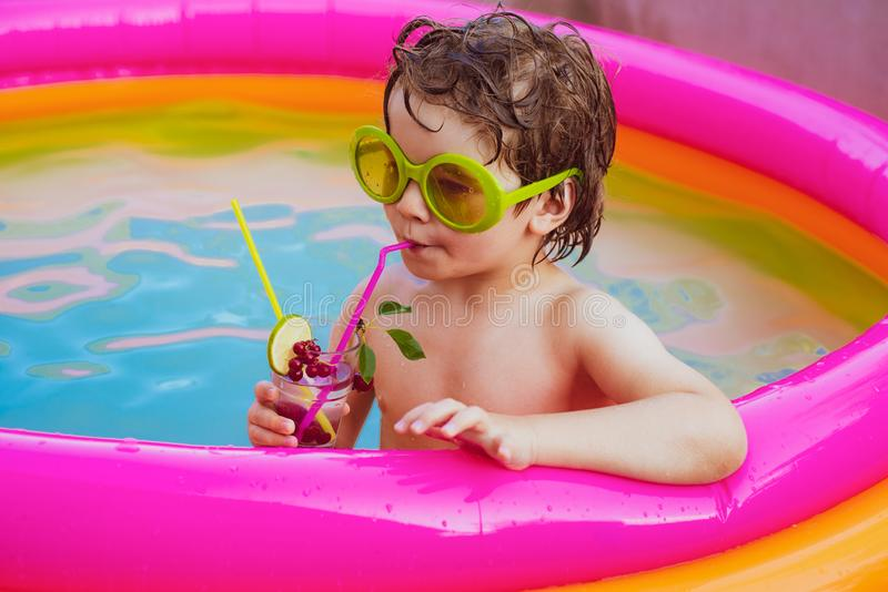 Little child boy relaxing in resort swimming pool and drinking cocktails. Cute kids relaxed and drink cocktail in royalty free stock images