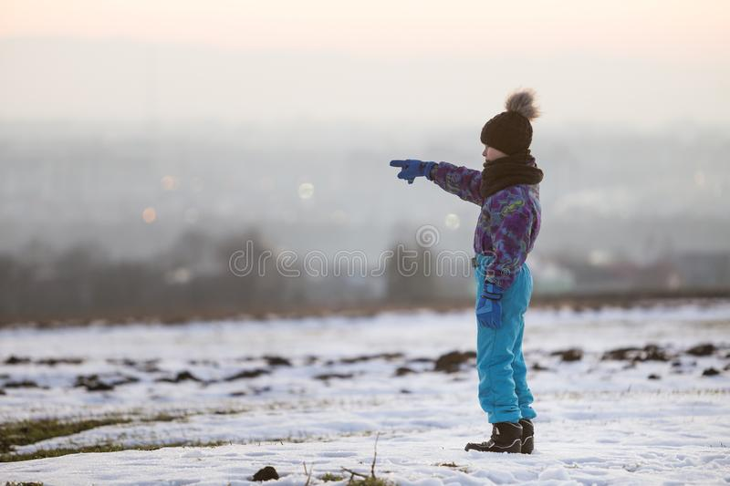Little child boy standing outdoors alone on snow covered winter field royalty free stock photography