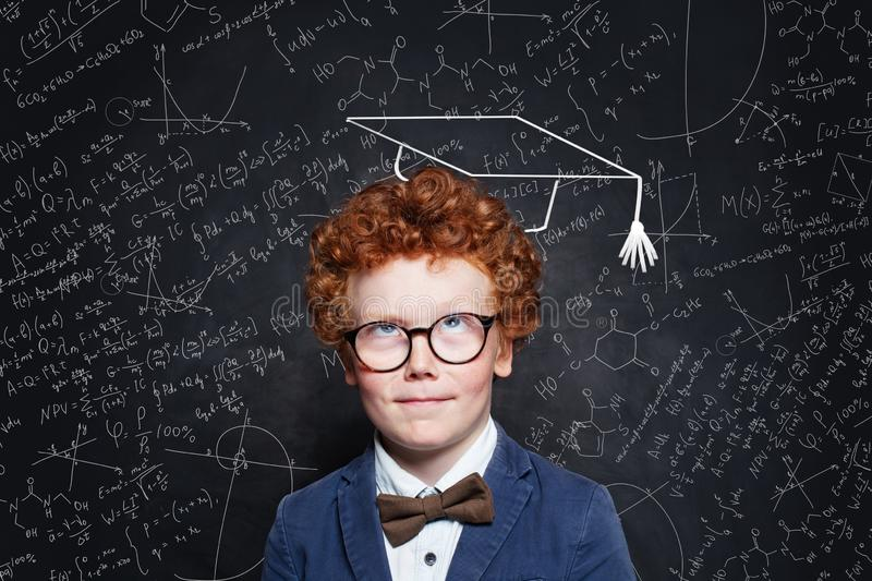 Little child boy thinking on blackboard background. Brainstorming and idea concept.  stock photo