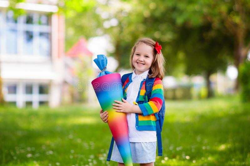 Little child with candy cone on first school day stock images