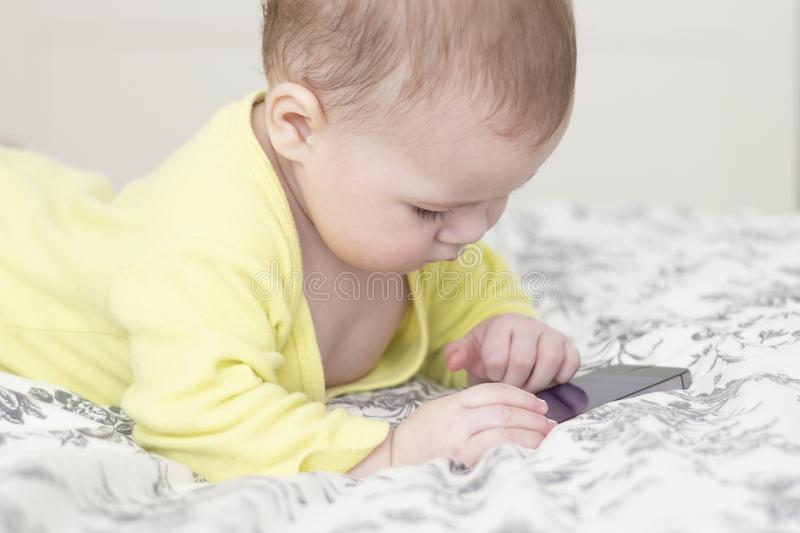Little child with a cell phone. Baby 7 months interested in the smartphone, lies on the bed and pokes a finger at the screen of. The smartphone. Kid in yellow stock photography