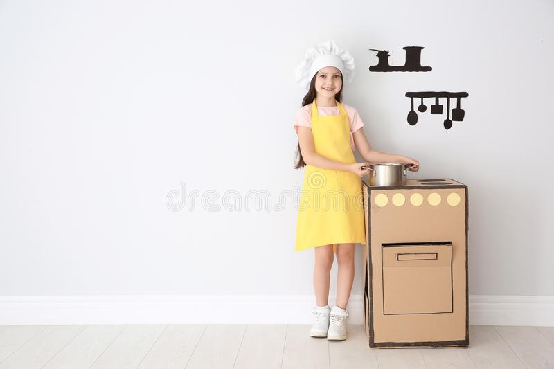 Little child in chef hat playing with carton stove royalty free stock photography