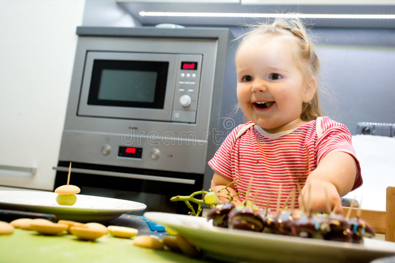Little child chief cooking cookies in the kitchen stock photos