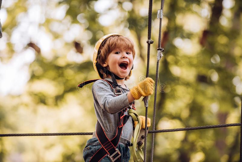 Little child climbing in adventure activity park with helmet and safety equipment. Toddler climbing in a rope playground royalty free stock photography