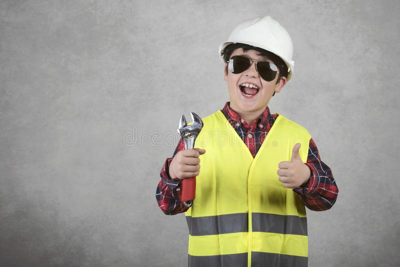 Little child construction worker in White helmet and sunglasses and holding a wrench royalty free stock images