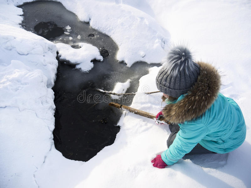 Little Child And Cracked Ice. Little child playing near a cracked ice on a lake, concept of a risk and danger royalty free stock photography