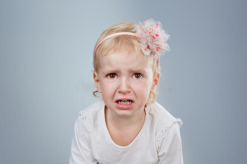 Little child is crying. Crying girl on grey background. Studio shot royalty free stock images
