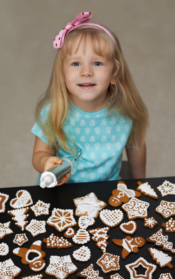 Little child decorating cookies with icing.  stock photo