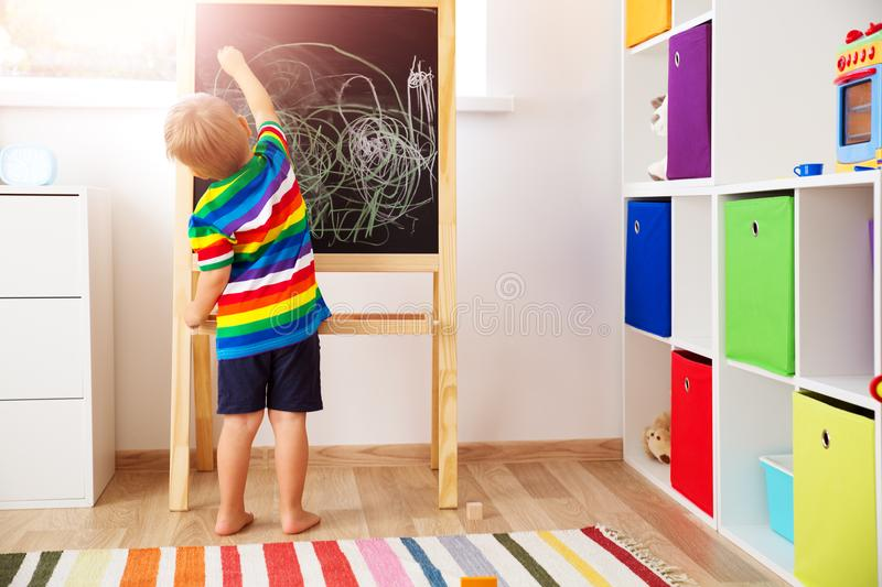Little child drawing on the blackboard. Boy standing in the room with chalkboard stock image